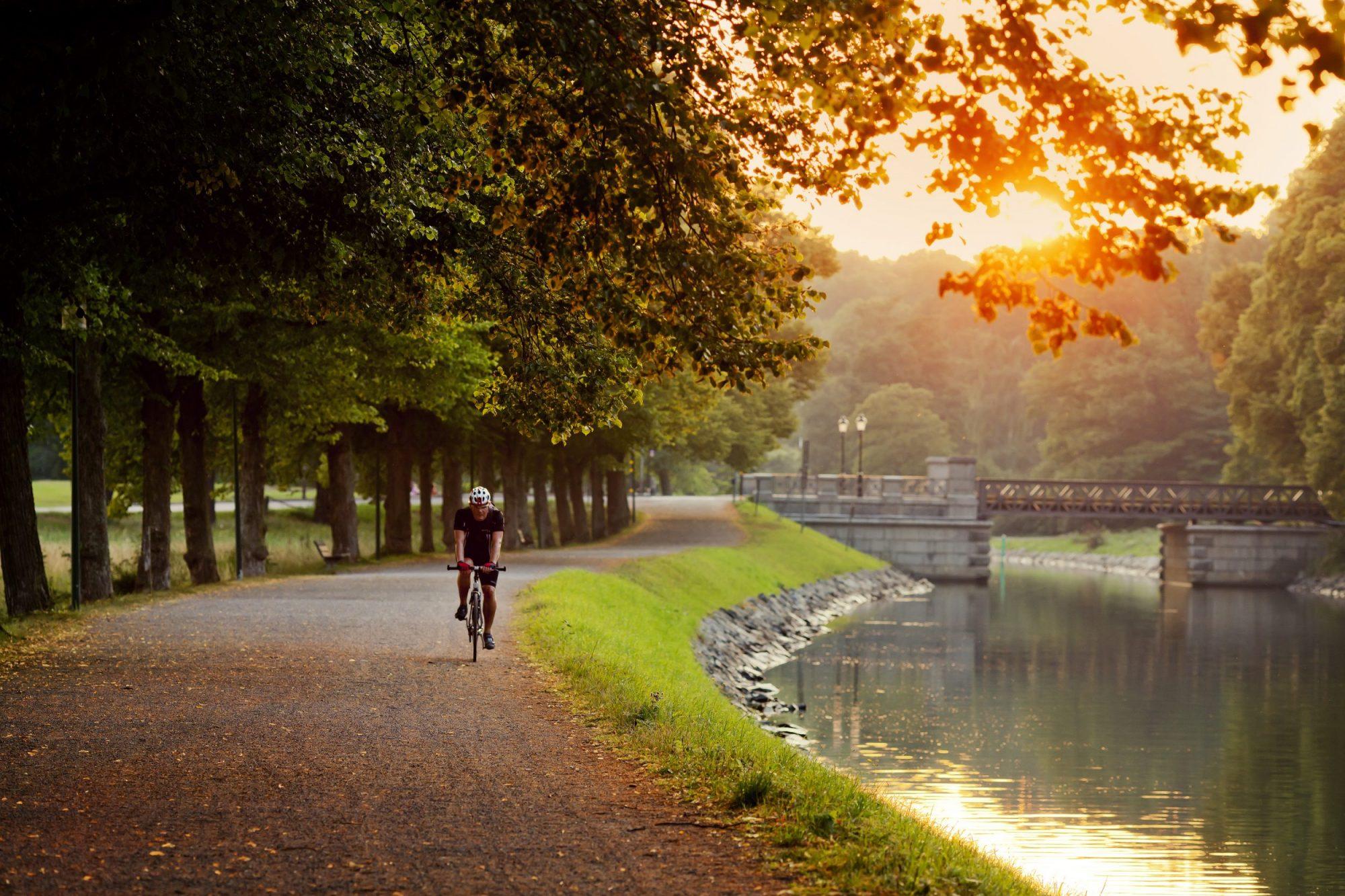 Man biking next to river