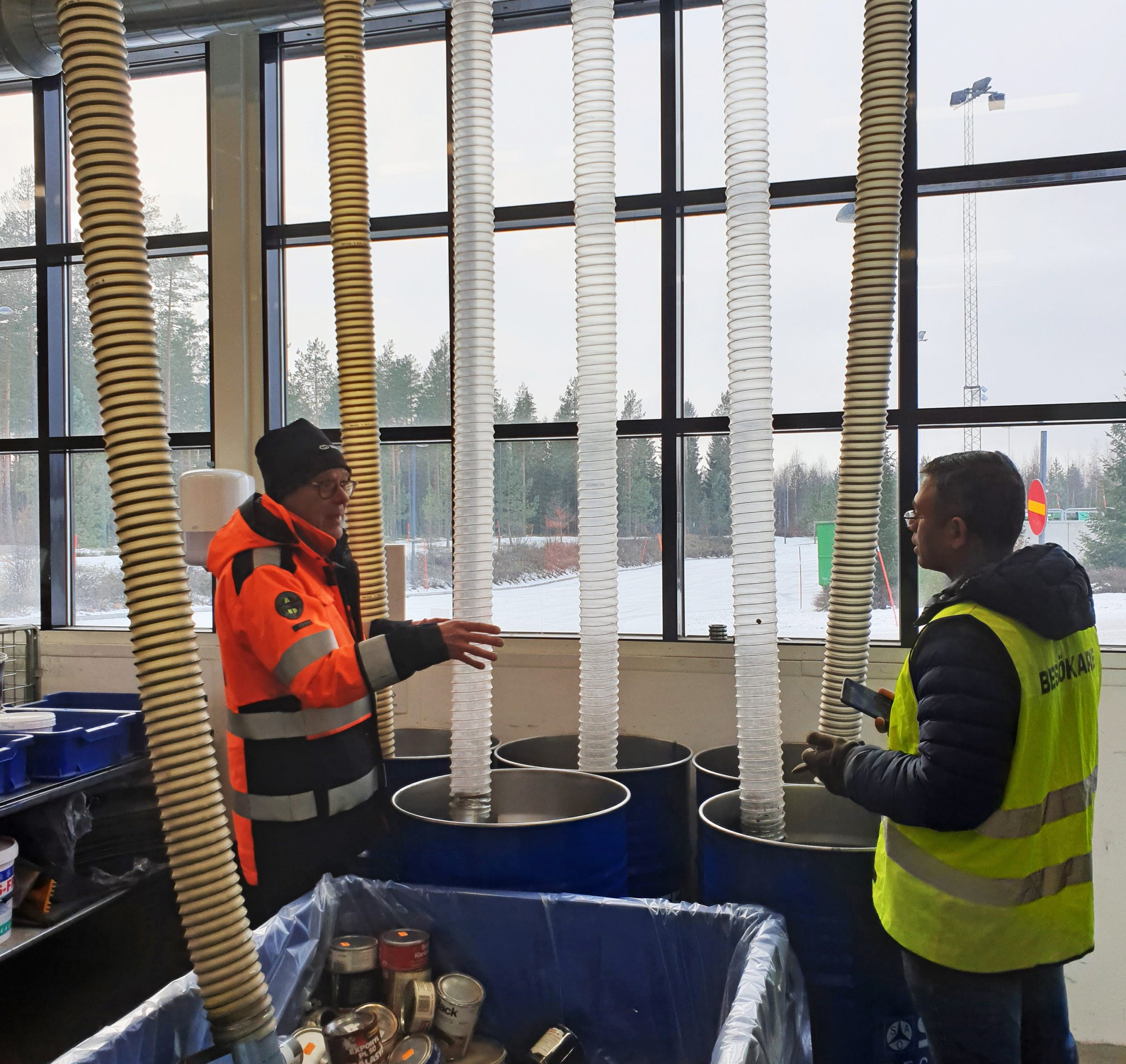 Two men discussing at recycling plant